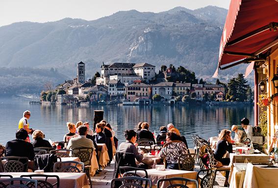 Italienisches Flair. Personen im Gastgarten am Meer. Gemütliches, stressfreies Essen
