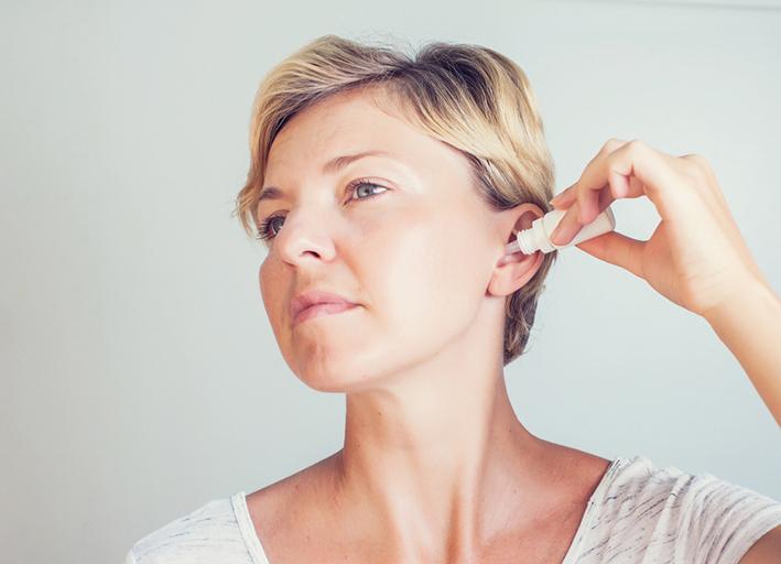 Frau tropft sich Ohrentropfen in Ohren. Gesundheitsratgeber im Mai