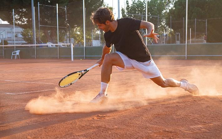 Mann spielt Tennis und geht in die Knie. Gelenkschmerzen