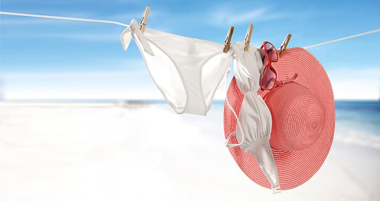 Weißer Bikini und roter Sonnenhut auf Wäscheleine am Strand. Scheideninfektion.