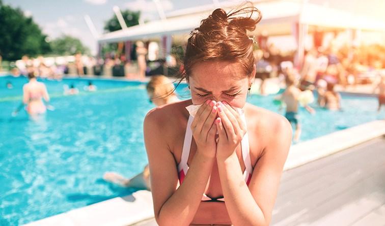 Frau im Bikin am Pool schnäuzt sich. Sommergrippe vorbeugen