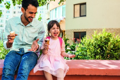 Vater mit Tochter beim Eisessen im Freien. Glückliches Kind. Fit für die Schule