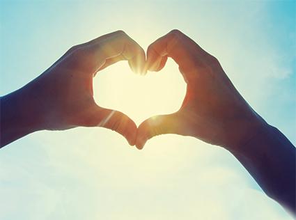 Hände formen Herz vor Sonne. Herz-Kreislauf-System