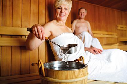Paar sitzt in Sauna. Machen Aufguss. Regeneration
