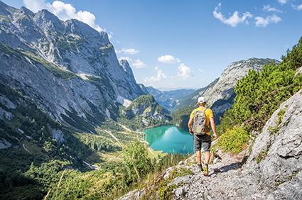 Mann wandert im Gebirge zu See. Wandertipps
