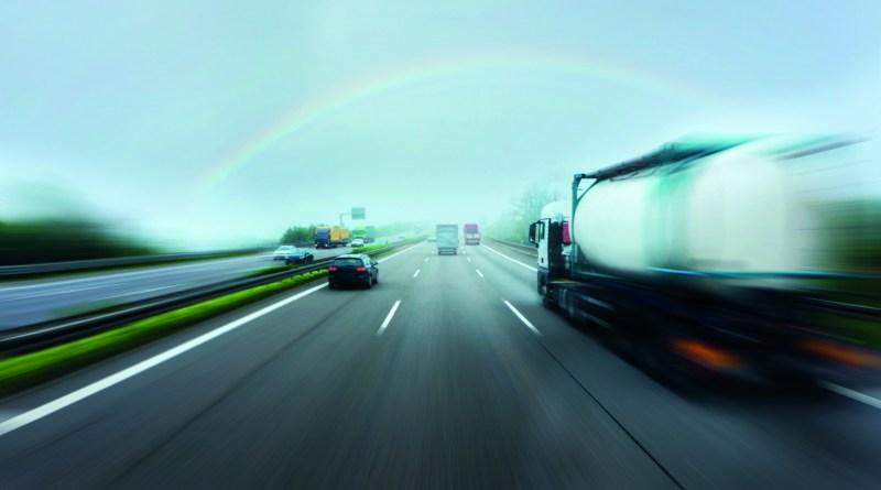 Vorbeifahrende Autos auf Straße. Regenbogen in Sicht. Verschwommene Autos. Sehqualität verbessern