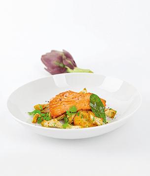 Lachsschnitzel auf Artischocken-Kartoffel-Gröstl angerichtet in weißem Teller. Rezepte aus Südtirol