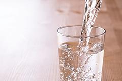 Wasser wird in Glas eingefüllt. Wasserglas. Gesundheitsratgeber im Dezember