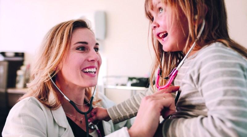 Weibliche Doktorin untersucht Kind mit Stetoskop. Erkältungstipps
