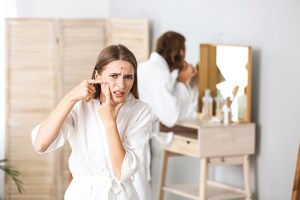 Frau im Badezimmer drückt Pickel aus. Mann hinter ihr drückt Pickel aus. Paar im weißen Bademantel. Akne vorbeugen