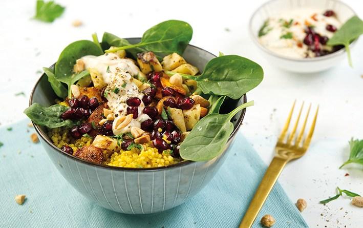 Gemüse-Quinoa-Bowl mit Erdnuss-Dip in Schüssel angerichtet. goldene Gabel. Clean Eating