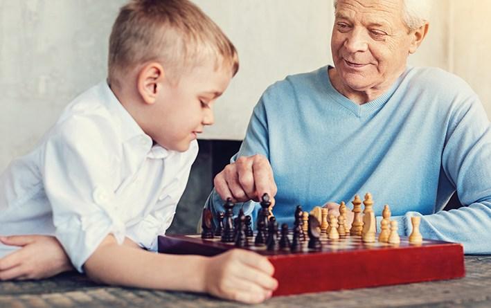 Opa spielt mit Enkelsohn Schach. Gedächtnisschwierigkeiten
