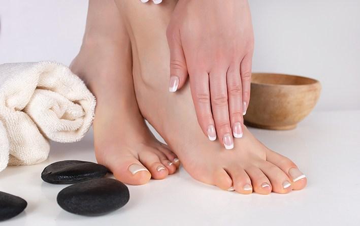Frau mit gepflegten Händen und Füßen auf weißem Hintergrund. gepflegte Füße