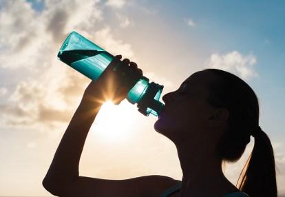 Frau trinkt aus Wasserflasche im Freien. Sonne scheint. schöne Haut