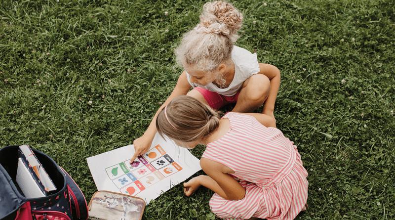 Kinder lernen im Gras mit Bildern. für einen erfolgreichen Schulstart