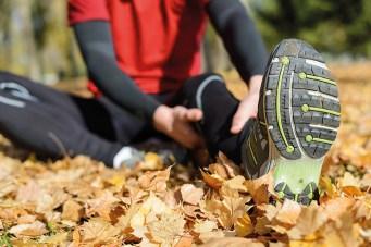 Sportler sitzt im Laub. Herbst. hält sich den fuß. Überbelastung. Regenerieren nach dem Sport