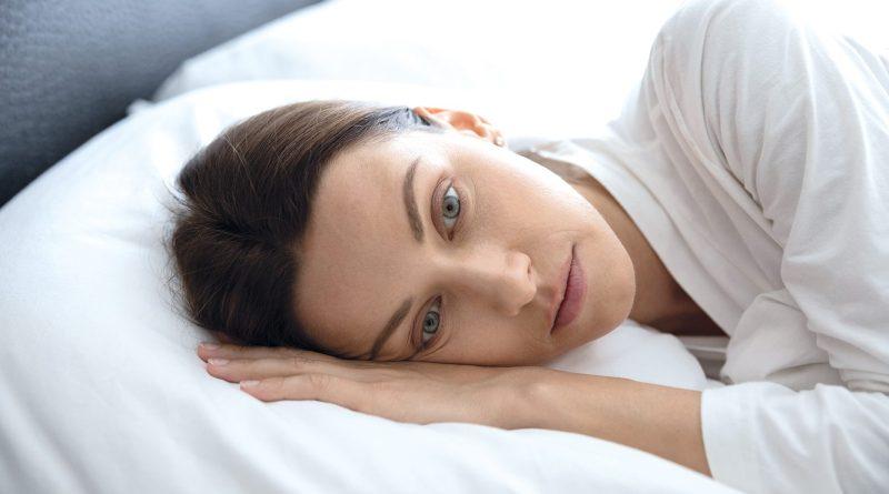 Schlafprobleme lösen. Frau liegt hellwach, aber müde im Bett. Weiße Laken. Schlaflos
