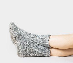 Füße mit grauen Wollsocken. Liegende Füße. Kalte Füße. Gesunde Atemwege