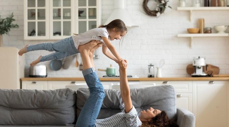Mutter liegt am Rücken auf Couch und nimmt Tochter mit Füßen hoch. Flieger. Energie und Vitalität. Energievolle Mutter