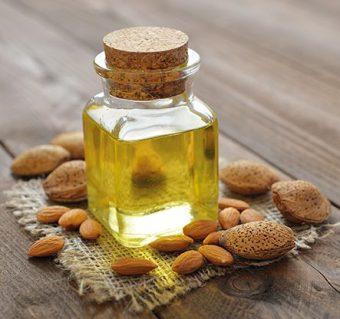 Mandelöl in Glasflasche auf Jutefleck. Holztisch. Mandeln und Nüsse verteilt. Trockene Haut und Jurckeiz