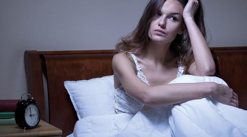 Frau sitzt im Bett, kann nicht schlafen. Es ist Mitten in der Nacht. Schlaflos