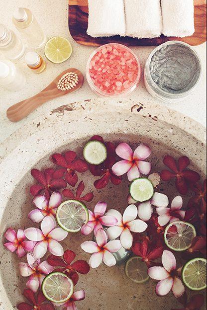 Fuß- und Handbad mit tropischen Blumen, Zitronen und Salzen. Handhyiene. Handbad in Schüssel