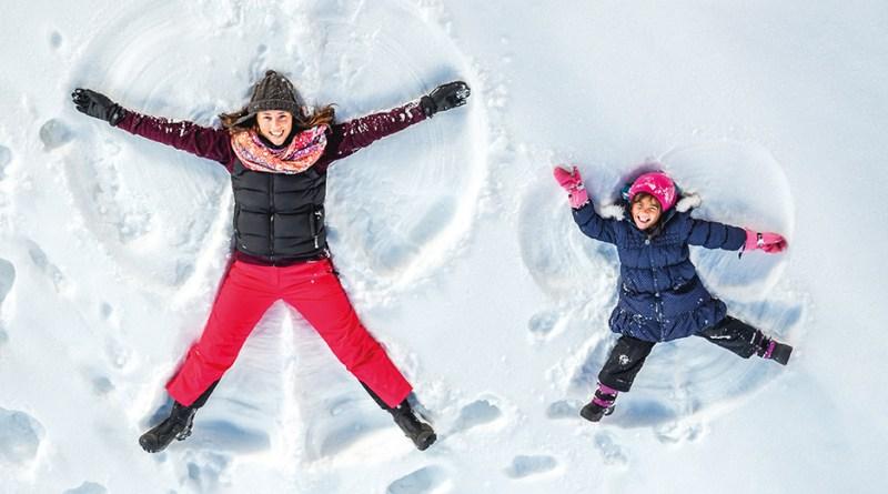 Mutter und Tochter machen Schneeengel im Schnee. Winter. Schutz vor Coronaviren