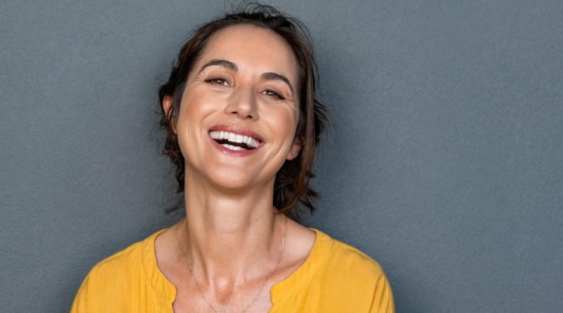 Lachende Frau in gelbem T-Shirt vor grauem Hintergrund. Zahnfleischprobleme