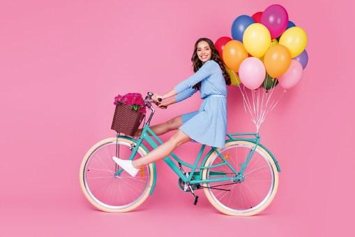Frau auf Fahrrad mit Luftballons. leichte Beinen. Venengesundheit