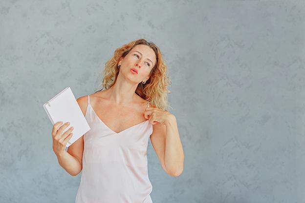 Schöne Frau fächert mit Notizblock in Hitze. Hitzewallung und Schweißausbrüche