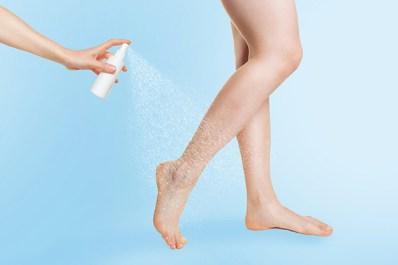 Kühlender Venenspray sprüht auf Wade vor blauem Hintergrund. Frauenbeine. Schöne Beine. Geschwollene Beine im Sommer