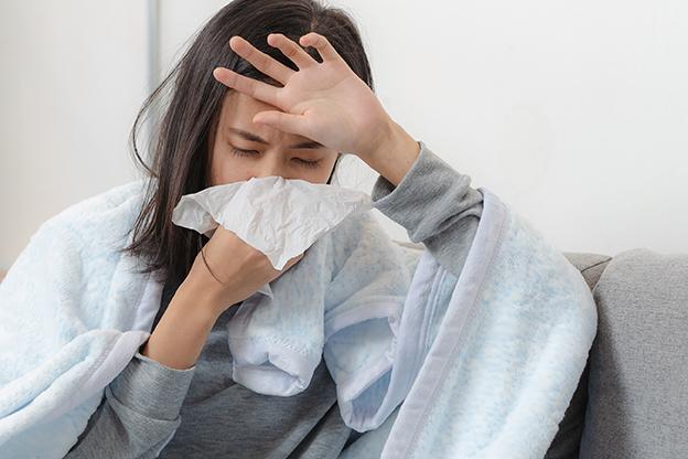 Kranke Frau zu Hause auf Sofa. Erkältung. Schnupfen oder Corona