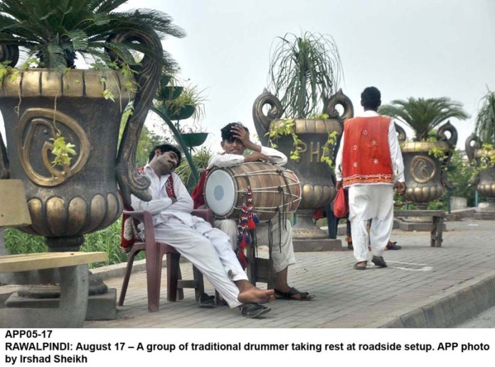 RAWALPINDI: August 17 – A group of traditional drummer taking rest at roadside setup. APP photo by Irshad Sheikh