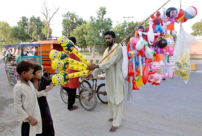 BAHAWALPUR: August 21 – A man selling out air-filled toys outside Bahawalpur Zoo. APP photo by Hassan Bukhari