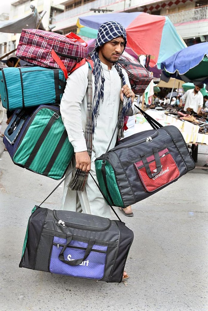 RAWALPINDI: August 24 - A vendor carrying and displaying bags to attract customers at Bara Market. APP photo by Abid Zia