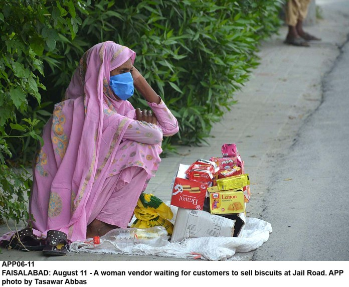 FAISALABAD: August 11 - A woman vendor waiting for customers to sell biscuits at Jail Road. APP photo by Tasawar Abbas