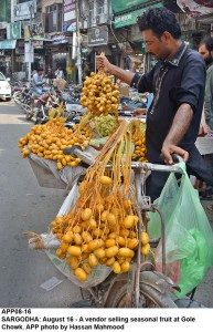 SARGODHA: August 16 - A vendor selling seasonal fruit at Gole Chowk. APP photo by Hassan Mahmood