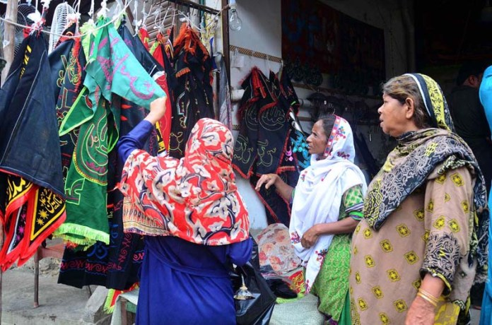 HYDERABAD: August 22 – Ladies selecting & purchasing Muharram procession related stuff from a vendor shop during Muharram-Ul-Haram. APP photo by Farhan Khan