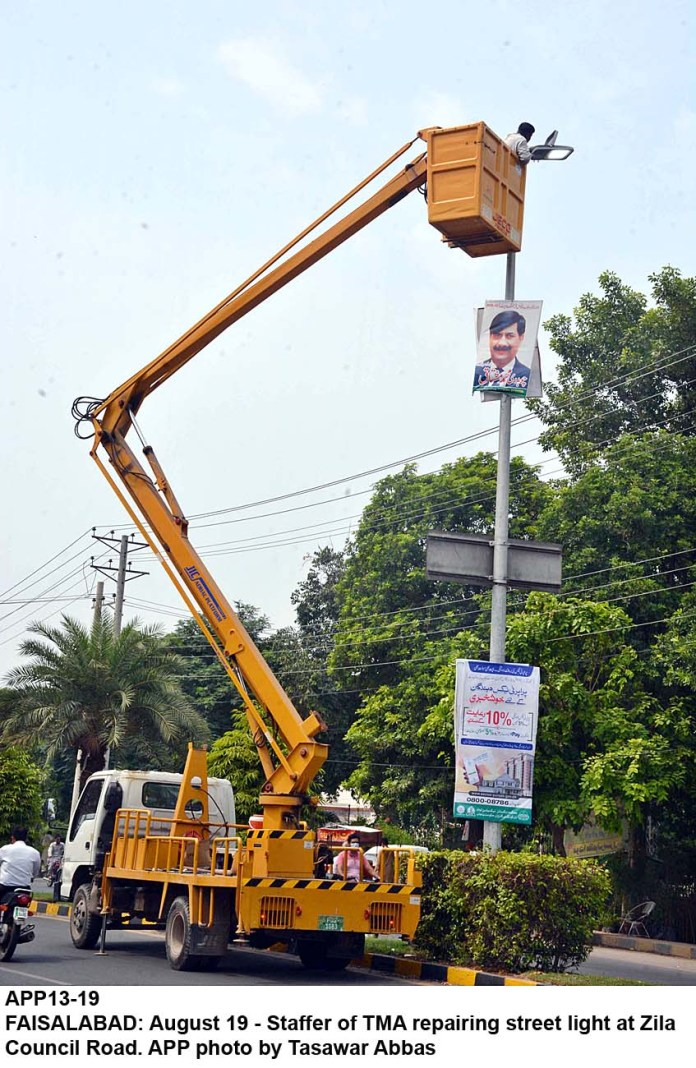 FAISALABAD: August 19 - Staffer of TMA repairing street light at Zila Council Road. APP photo by Tasawar Abbas