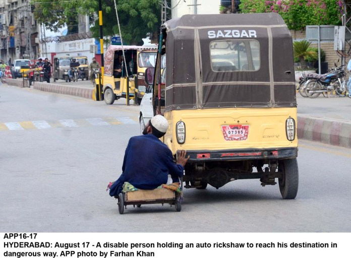 HYDERABAD: August 17 - A disable person holding an auto rickshaw to reach his destination in dangerous way. APP photo by Farhan Khan