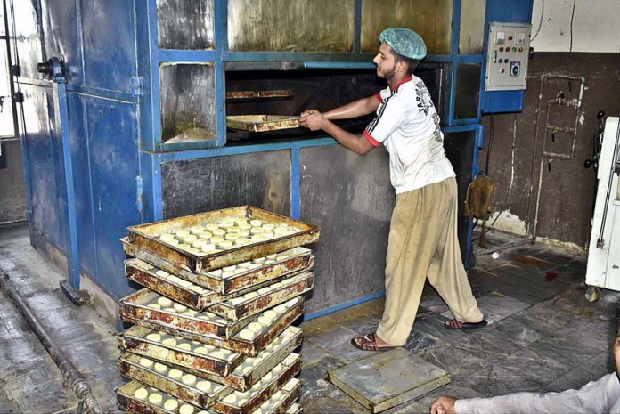 FAISALABAD: August 25 - A worker busy in making food items at a bakery. APP photo by Muhammad Waseem