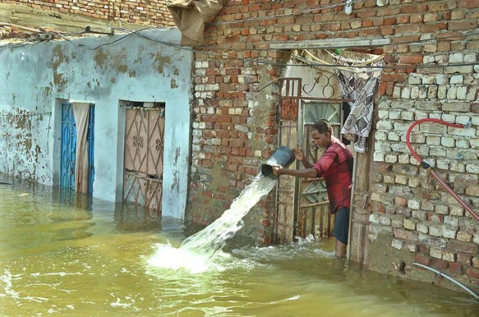 HYDERABAD: August 26 – Resident of Railway Colony throwing water out of the house as water enters their houses due to heavy rain. APP photo by Akram Ali