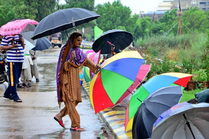 HYDERABAD: August 31 – A woman vendor displaying umbrellas on footpath to attract the customers at Qasimabad during rain that experienced the city. APP photo by Farhan Khan
