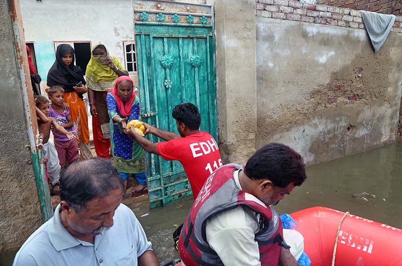 HYDERABAD: August 26 - Edhi workers distribution food to rain affected area of Mehar Ali Shah Colony due to heavy rain. APP photo by Akram Ali