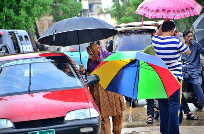 HYDERABAD: August 31 – A woman vendor selling umbrellas to customers at Qasimabad during rain that experienced the city. APP photo by Farhan Khan