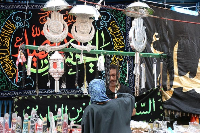 KARACHI: August 24 - A woman busy in selecting Muharram related items from shopkeeper near Nishtar Park. APP Photo by M Saeed Qureshi
