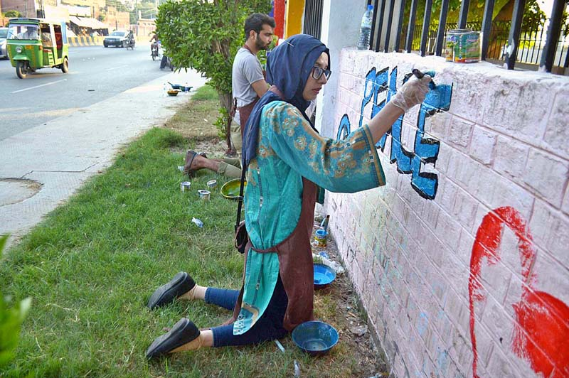 MULTAN: August 24 - Arts students of Bahauddin Zakariya University busy in painting on the wall to add beautification in the city. APP photo by Safdar Abbas