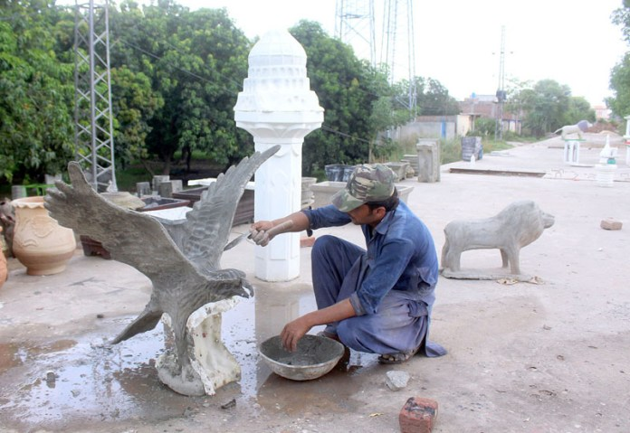 MULTAN: August 28 - Labourer busy in giving final touch to an eagle sculpture at his workplace. APP photo by Tanveer Bukhari