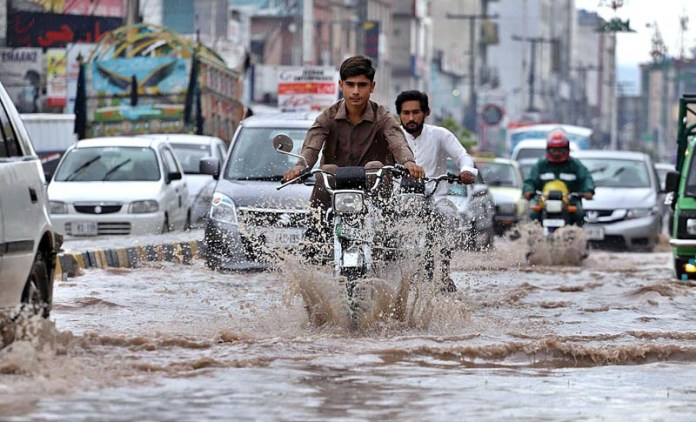 RAWALPINDI: August 31 - Motorcyclist passing through rain water accumulated on the road during rain at Railway Road. APP photo by Abid Zia