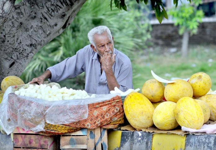 MULTAN: August 27 - An elder vendor displaying seasonal fruit to attract the customer while sitting at footpath. APP photo by Qasim Ghauri